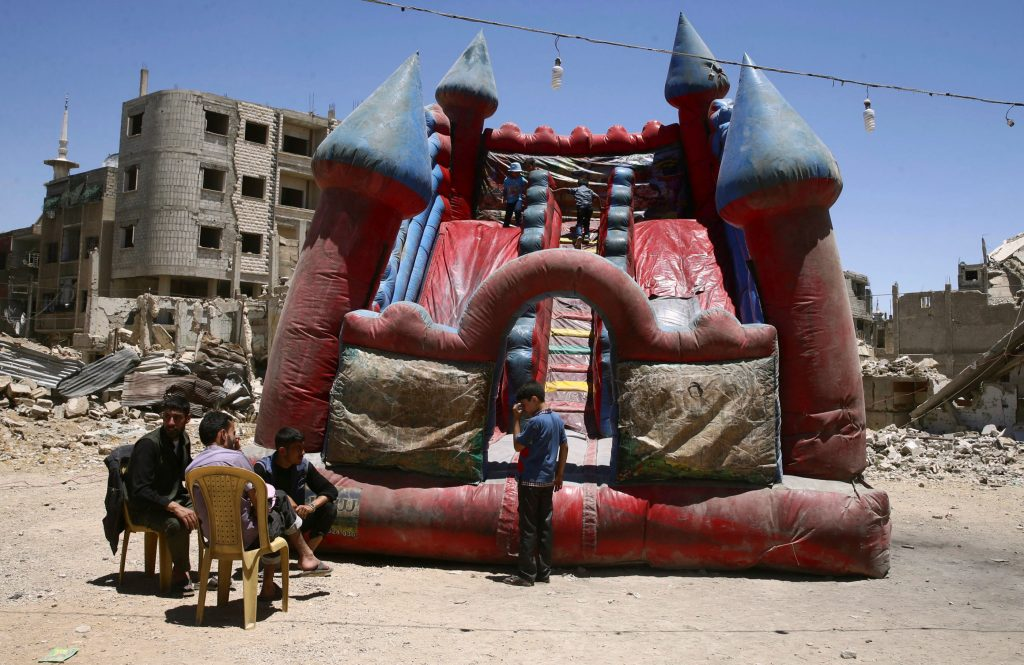Children play inside an inflatable castle during Eid al-Fitr celebration in the rebel-held Douma neighborhood of Damascus in June. Photo by Bassam Khabieh/Reuters