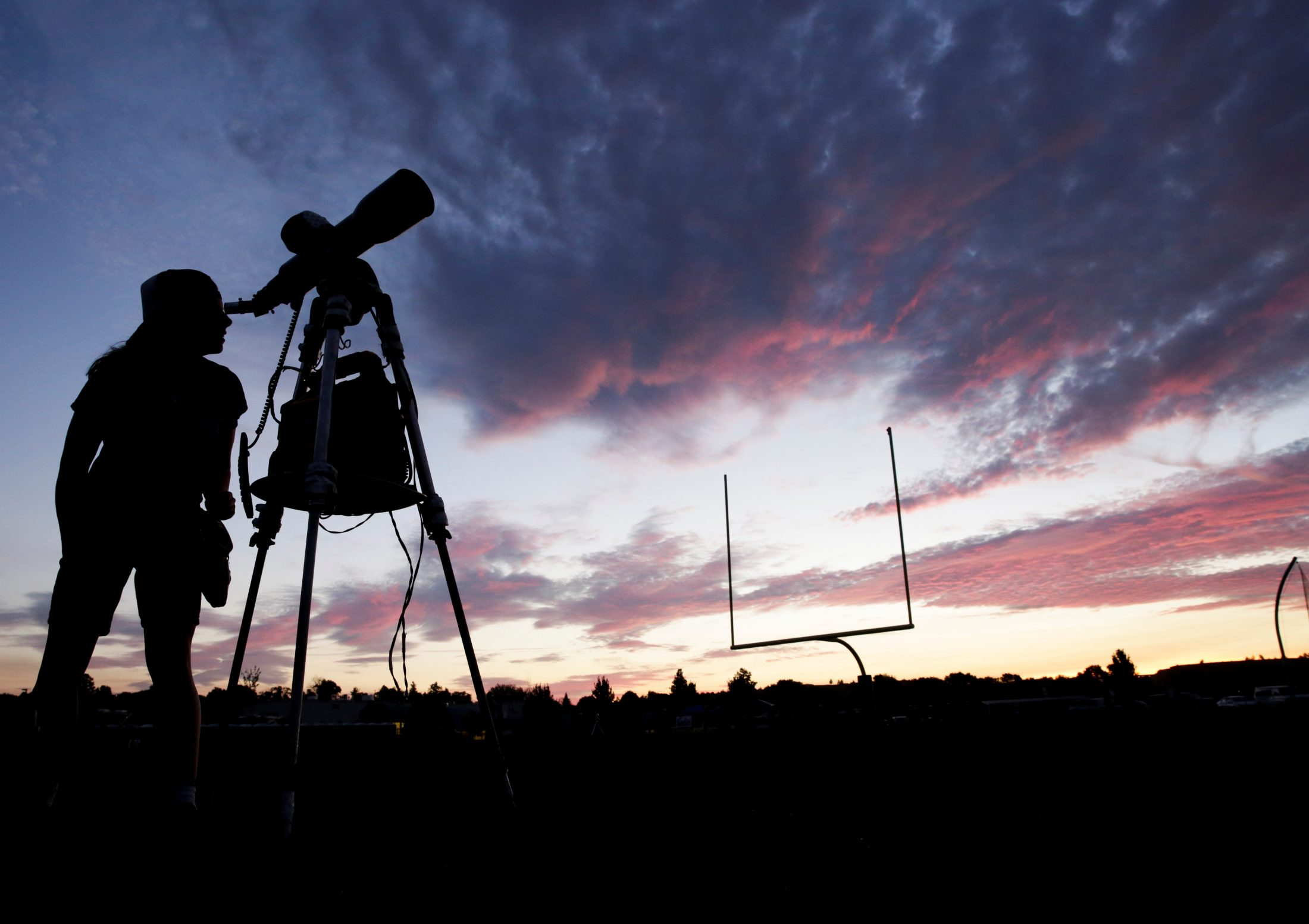 A woman looks through a telescope on the football field at Madras High School the evening before a solar eclipse in Madras, Oregon. Photo by Jason Redmond/Reuters