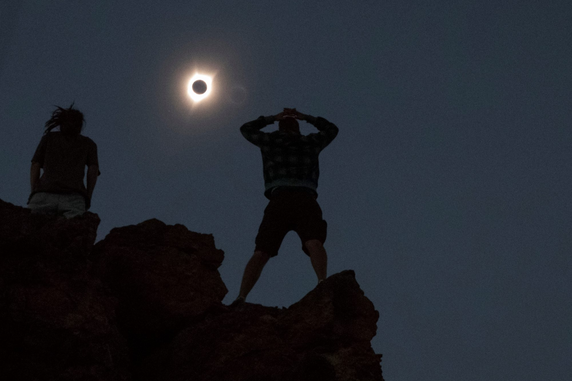 Tanner Person (R) and Josh Blink watch the total solar eclipse while standing atop Carroll Rim Trail at Painted Hills, a unit of the John Day Fossil Beds National Monument, near Mitchell, Oregon. Photo by Adrees Latif/Reuters