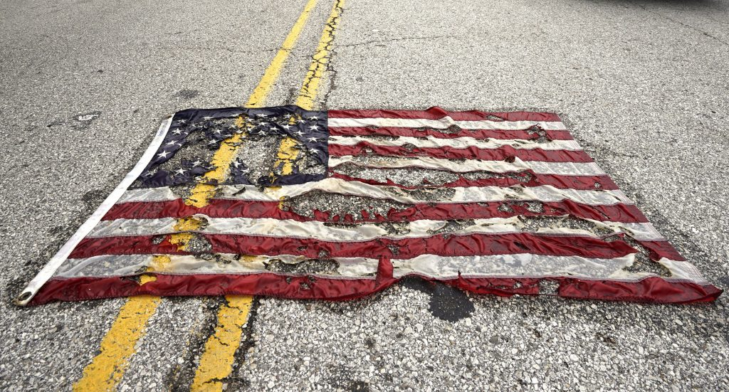 A partially burned American flag lies on the street near the spot where Michael Brown was killed before an event to mark the one year anniversary of his killing in Ferguson, Missouri August 9, 2015.  Several hundred people gathered in Ferguson on Sunday to mark the anniversary of the shooting death of the unarmed black teenager by a white police officer that sparked protests and a national debate on race and justice.  REUTERS/Rick Wilking - RTX1NP45