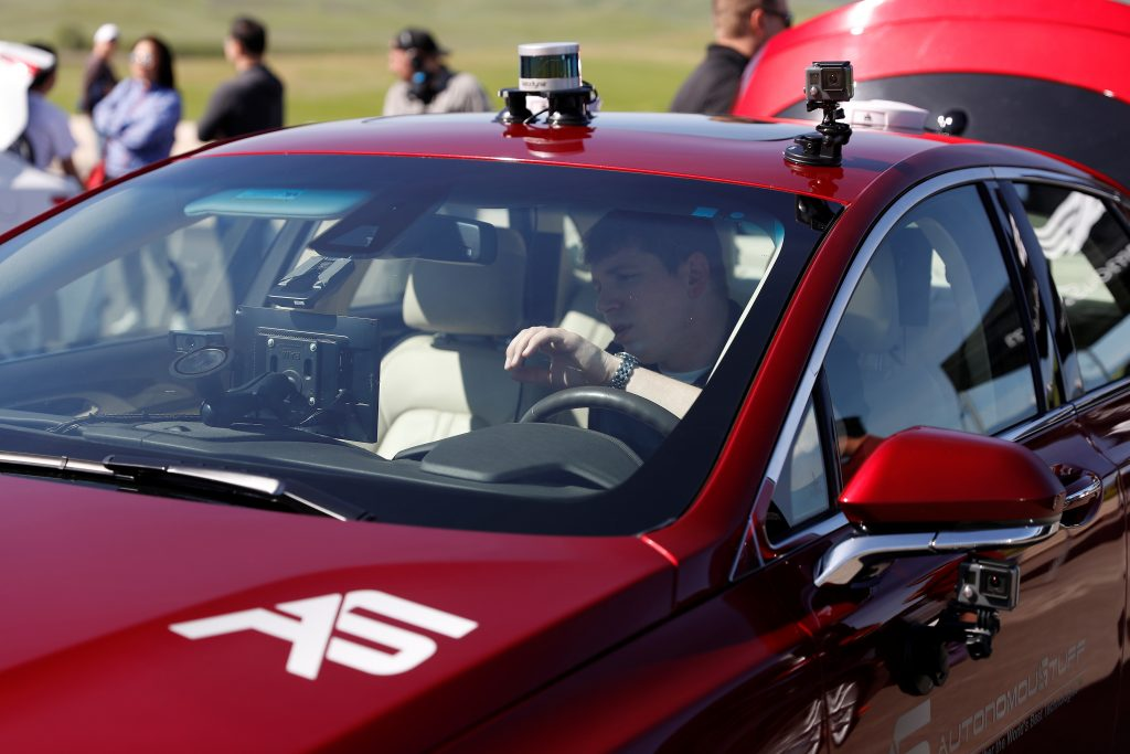 An engineer works on an AutonomouStuff Automated Research Development Vehicle during a self-racing cars event at Thunderhill Raceway in Willows, California, U.S., April 1, 2017. REUTERS/Stephen Lam - RC1C476426B0