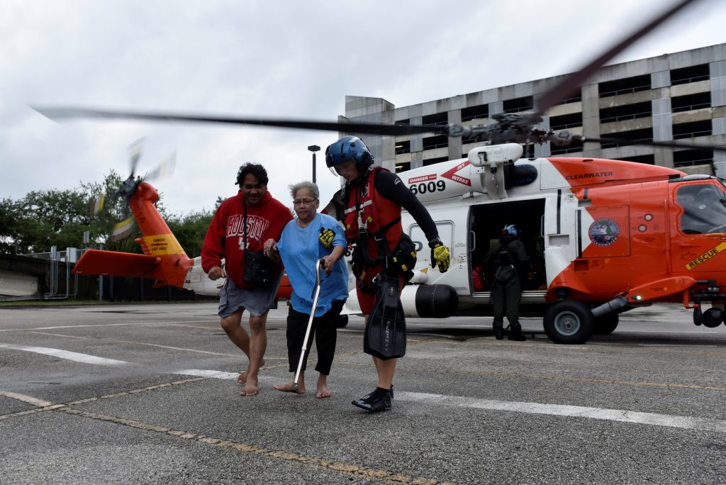 Evacuees Rickey Manuel (left) and Marjory Manuel (center) exit a U.S. Coast Guard helicopter that rescued them after Hurricane Harvey inundated the Texas Gulf Coast with rain and flooded their home in Houston, Texas, on Aug. 27. Photo by Nick Oxford/Reuters