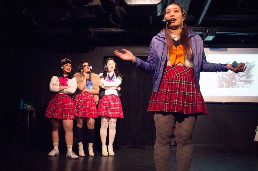 """Angel Yau performing a recurring gag where she talks about the atrocities the Japanese army committed during the """"Rape of Nanking."""" Iliana Inocencio, Maya Deshmukh, and Ann Marie Yoo (left to right) are standing behind her."""