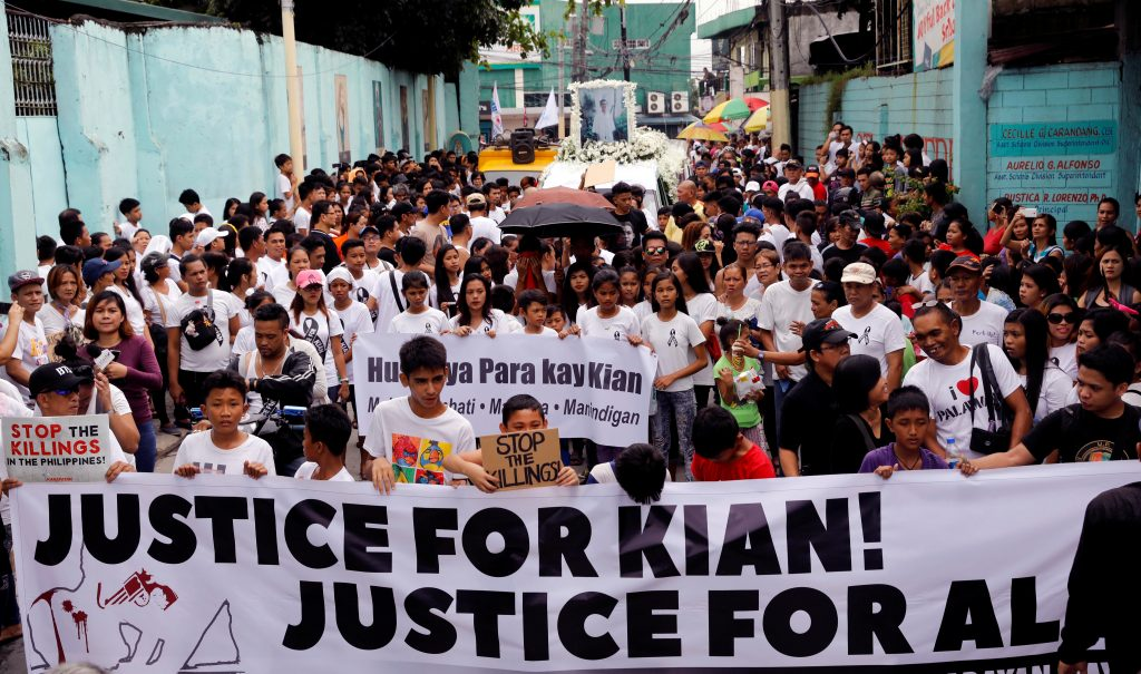 Mourners display a streamer during a funeral march for Kian delos Santos, a 17-year-old student who was shot during anti-drug operations in Caloocan, Metro Manila, Philippines August 26, 2017. REUTERS/Erik De Castro - RTX3DDW7