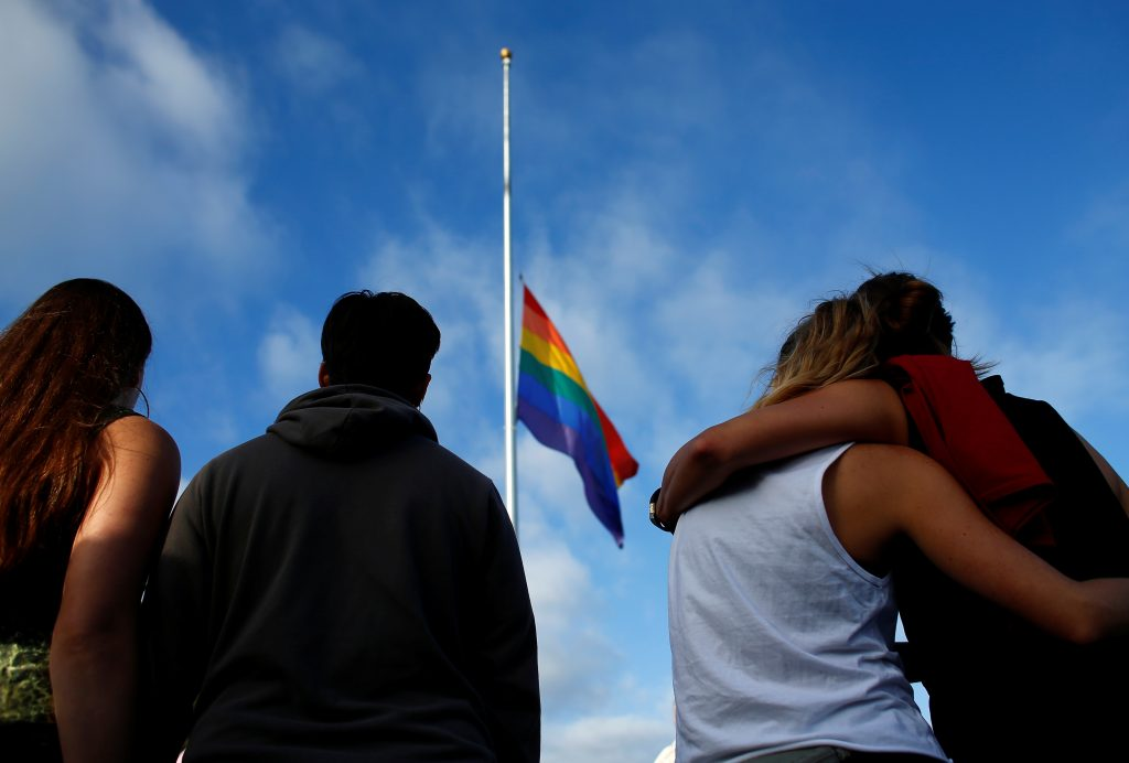 Mourners gather under a LGBT pride flag flying at half-mast for a candlelight vigil in remembrance for mass shooting victims in Orlando, from San Diego, California, U.S. June 12, 2016.  To match Special Report FLORIDA-SHOOTING/HATE CRIMES      REUTERS/Mike Blake/File Photo - RTX2IPWI