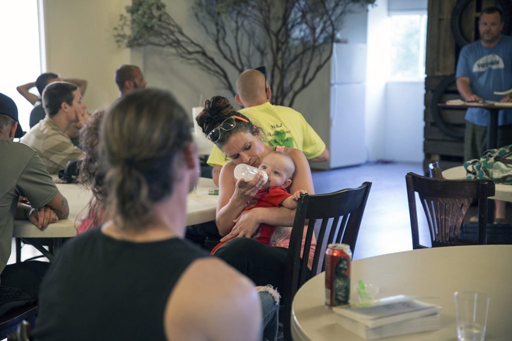 Heather Menzel feeds her daughter, Belle, during a Christian-based drug recovery meeting in Wofford Heights, California, in June 2016. Menzel is taking a maintenance dose of methadone to treat her heroin addiction. Photo by Brian Rinker for Kaiser Health News