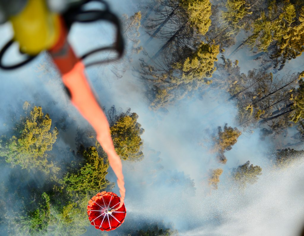 An Oregon Army National Guard Chinook helicopter dumps a 2,000 gallon capacity Bambi Bucket amid smoke over the Mt. Jefferson Wilderness area in order to support firefighting efforts on the Whitewater Fire in Oregon, U.S. on August 5, 2017. Picture taken on August 5, 2017. Courtesy Leslie Reed/Oregon National Guard/Handout via REUTERS ATTENTION EDITORS - THIS IMAGE HAS BEEN SUPPLIED BY A THIRD PARTY. - RTS1C5JW