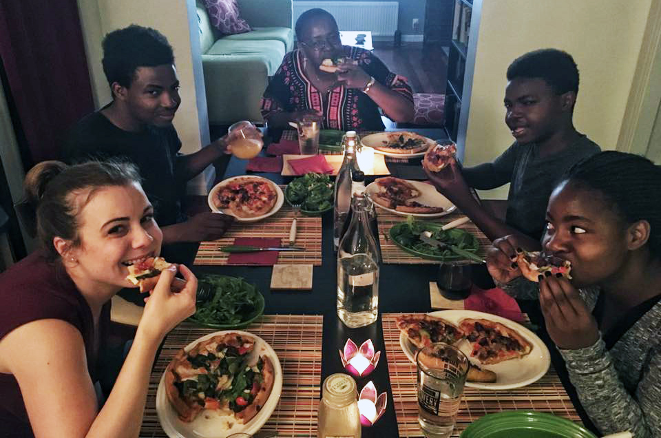 Kristin Garbarino (left) hosts a pizza dinner for a family from Rwanda. Photo by Richard Gartner