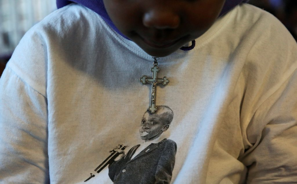 A child wears a cross over a top featuring the image of the late Nkosi Johnson, one of the youngest victims of the HIV epidemic and died in 2001 from the disease, during the launch of the 5-Day countdown ahead of the AIDS2016 International Conference, at the orphanage Nkosi's Haven, which was named after Johnson, in Johannesburg, South Africa July 13, 2016. REUTERS/Siphiwe Sibeko - RTSHP0Q