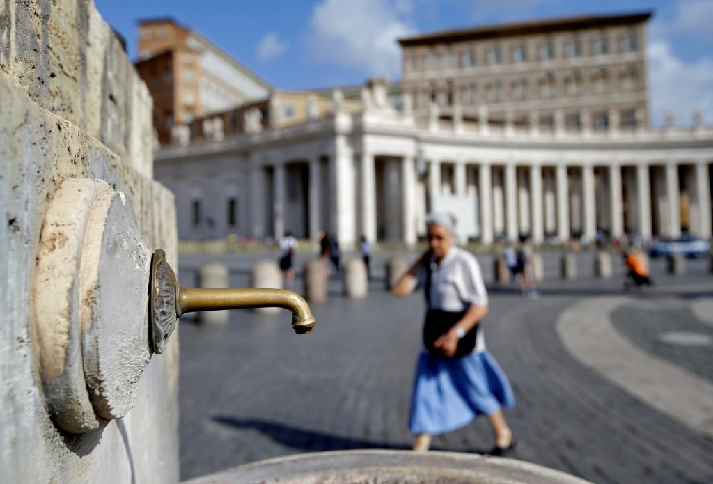 A woman walks next to a fountain in Saint Peter's Square at the Vatican July 25, 2017. REUTERS/Max Rossi - RTX3CSAS