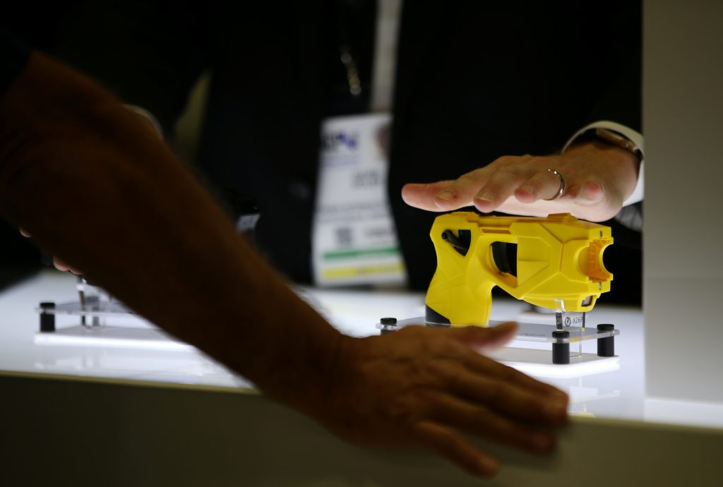 The Taser X26P gun is shown by a sales person to an attendee in the Taser booth at the International Association of Chiefs of Police conference in San Diego, California, U.S. October 17, 2016.  Picture taken October 17, 2016.  To match Special Report USA-TASER/EXPERTS   REUTERS/Mike Blake - RTS1D48Z