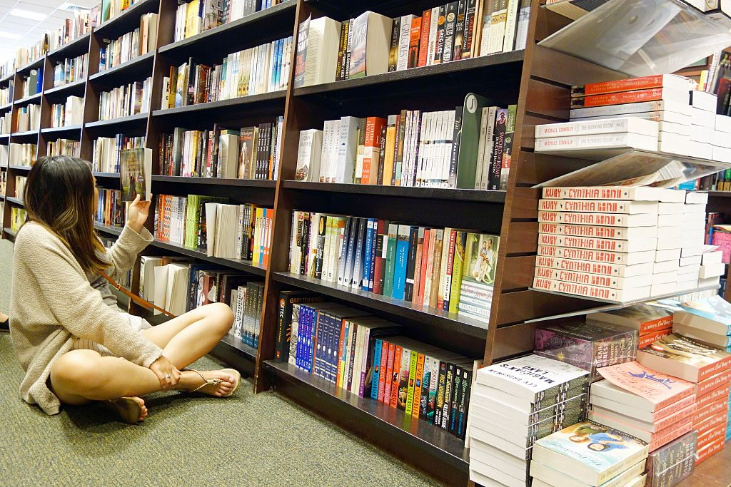 Woman Looking at Books in Bookstore, Boston, Massachusetts, United States. (Photo by: Education Images/UIG via Getty Images)