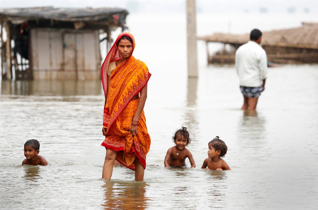 A woman walks through a flooded village in Motihari, Bihar State, in India on Aug. 23. Photo by Cathal McNaughton/Reuters