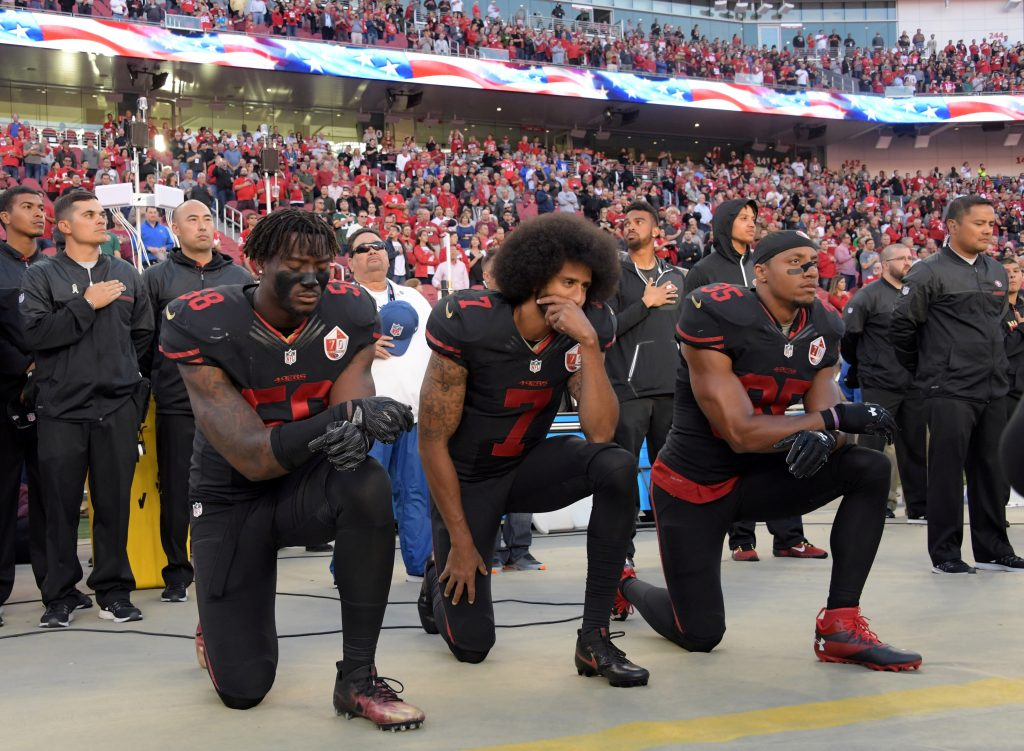 San Francisco 49ers outside linebacker Harold, quarterback Kaepernick and free safety Reid kneel in protest during the playing of the national anthem before a NFL game against the Arizona Cardinals in Santa Clara