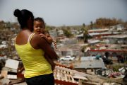Ysamar Figueroa carrying her son Saniel, looks at the damage in the neighborhood after the area was hit by Hurricane Maria, in Canovanas, Puerto Rico September 26, 2017. REUTERS/Carlos Garcia Rawlins