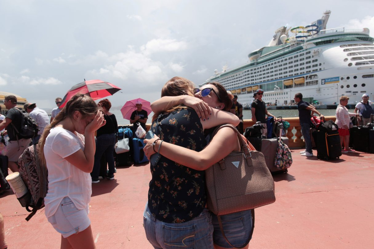 Women hug as people line up to board a Royal Caribbean cruise ship in San Juan that will take them to the U.S. mainland