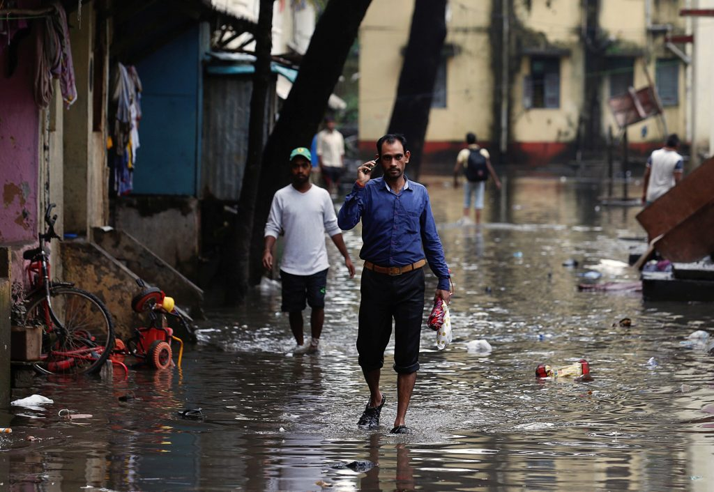 People walk through a flooded street in Mumbai, India, on Aug. 30. Photo by Danish Siddiqui/Reuters