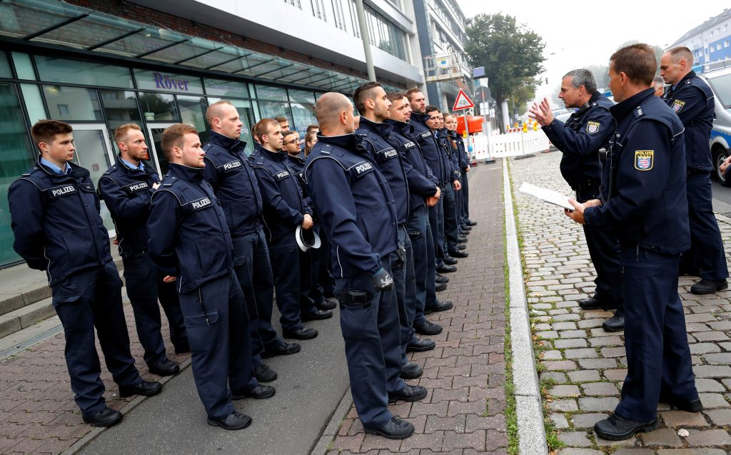 Police officers get their instructions as 60,000 people in Germany's financial capital are about to evacuate the city while experts defuse an unexploded British World War Two bomb found during renovations on the university's campus in Frankfurt