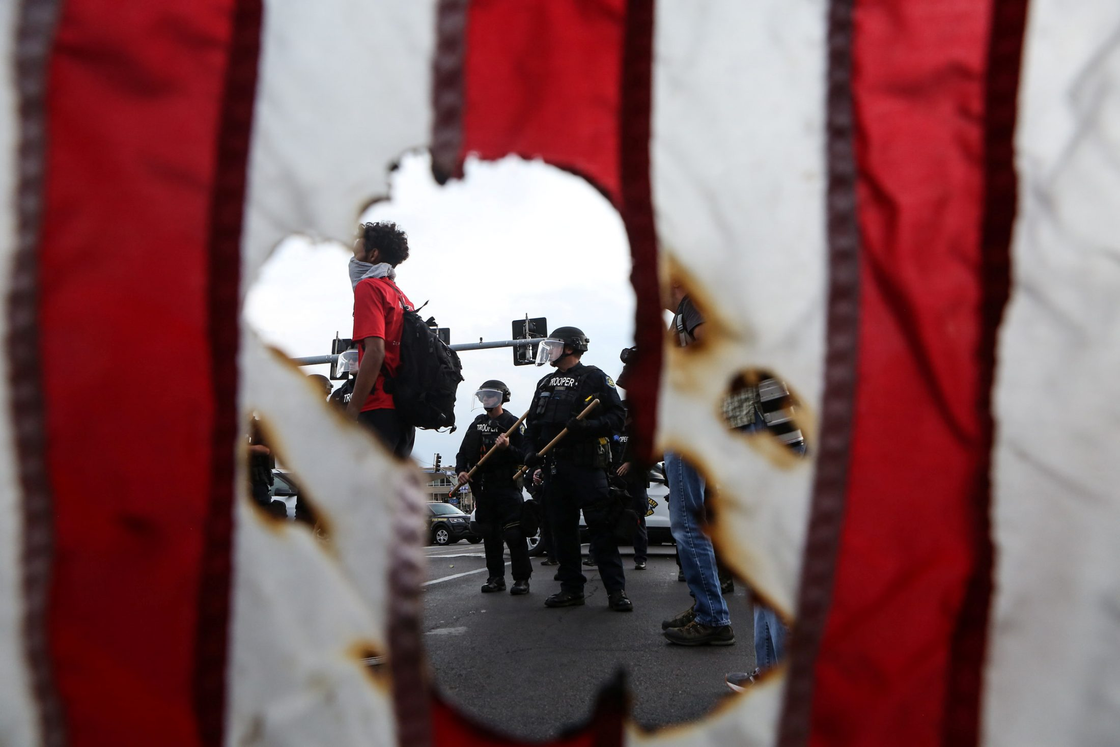 Police in riot gear and a protester stand near a burned U.S. flag after the not guilty verdict in the murder trial of Jason Stockley, a former St. Louis police officer charged with the 2011 shooting of Anthony Lamar Smith, in St. Louis, Missouri, U.S. Sept. 17. Photo by Lawrence Bryant/Reuters