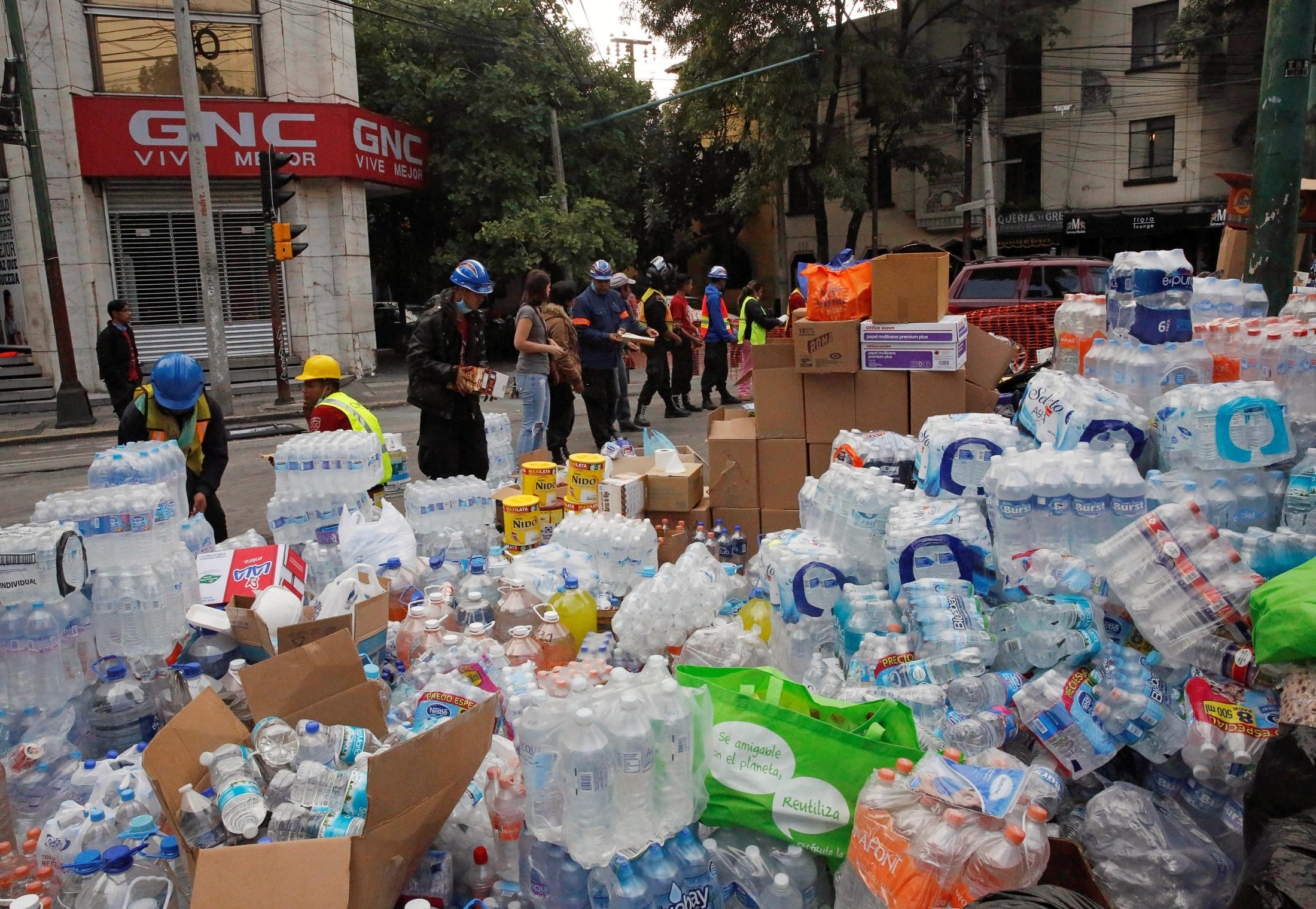 Piles of donations, including bottled water, are distributed after the earthquake. Photo by Henry Romero/Reuters