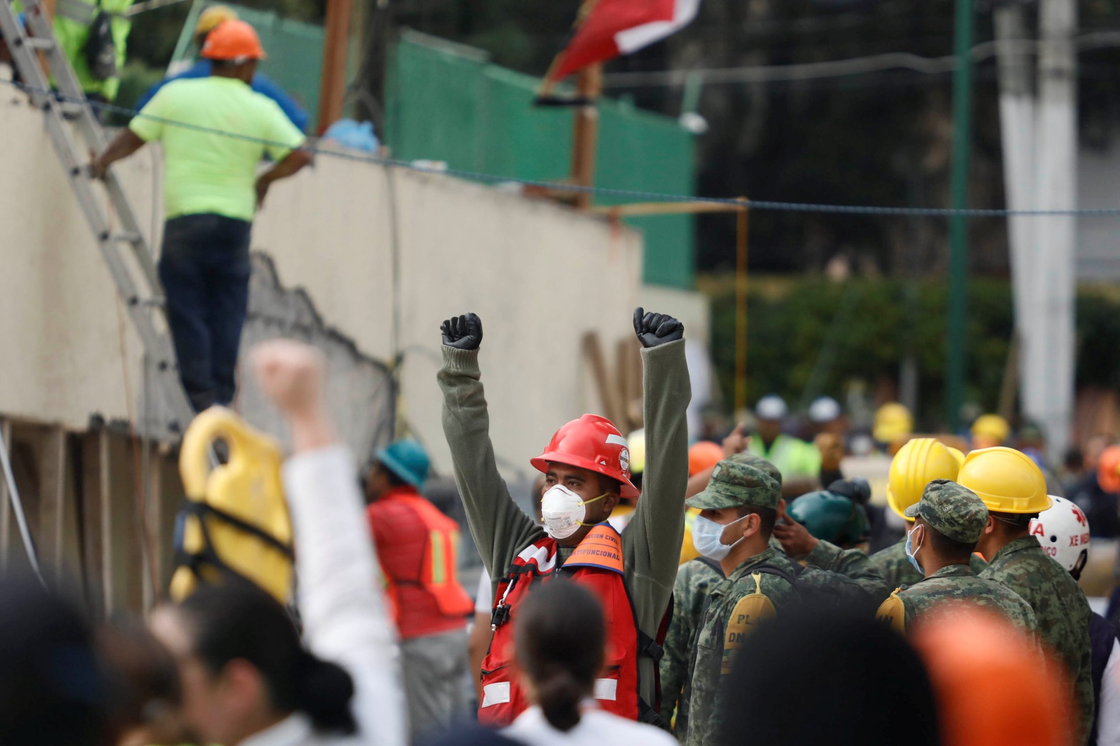 A rescue worker raises his hands to ask for silence during the search for students after an earthquake collapsed a school. Photo by Edgard Garrido/Reuters