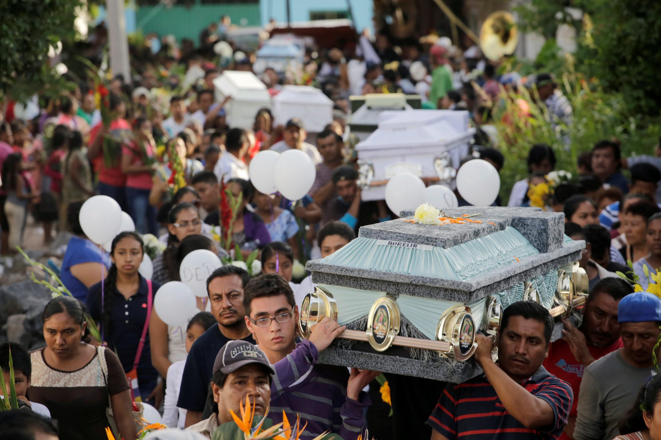 People carry caskets of earthquake victims through the streets in Atzala on the outskirts of Puebla, Mexico. Photo by Imelda Medina/Reuters