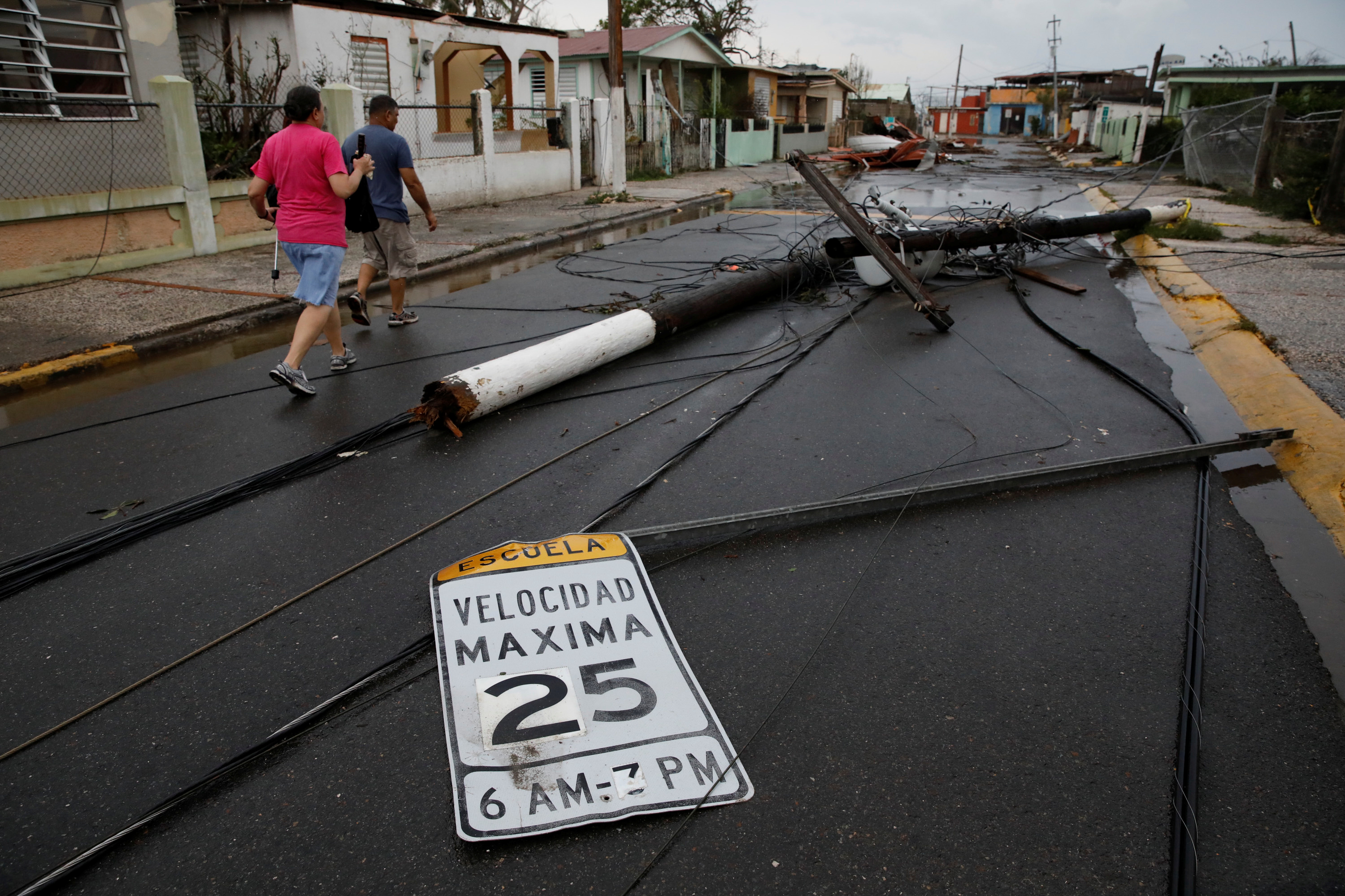 People walk next to fallen electric poles and traffic signs after the area was hit by Hurricane Maria in Salinas, Puerto Rico, September 21, 2017. REUTERS/Carlos Garcia Rawlins - RC160D8D2AF0