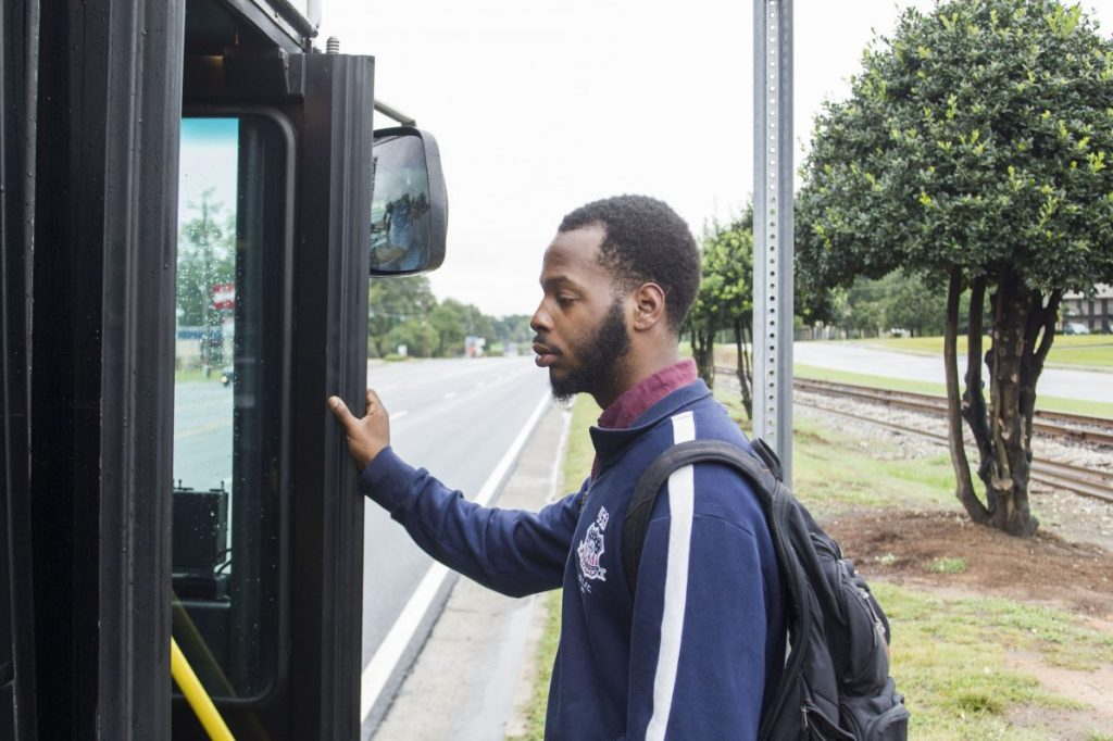After a 20-minute walk, and a 10-minute wait in the rain, DeAngelo Bowie catches the bus to get to work. Bowie, 24, dropped out of Georgia State after financial problems derailed him from his dream of becoming a history teacher. Photo: Chad Rhym/ Chad.Rhym@ajc.com