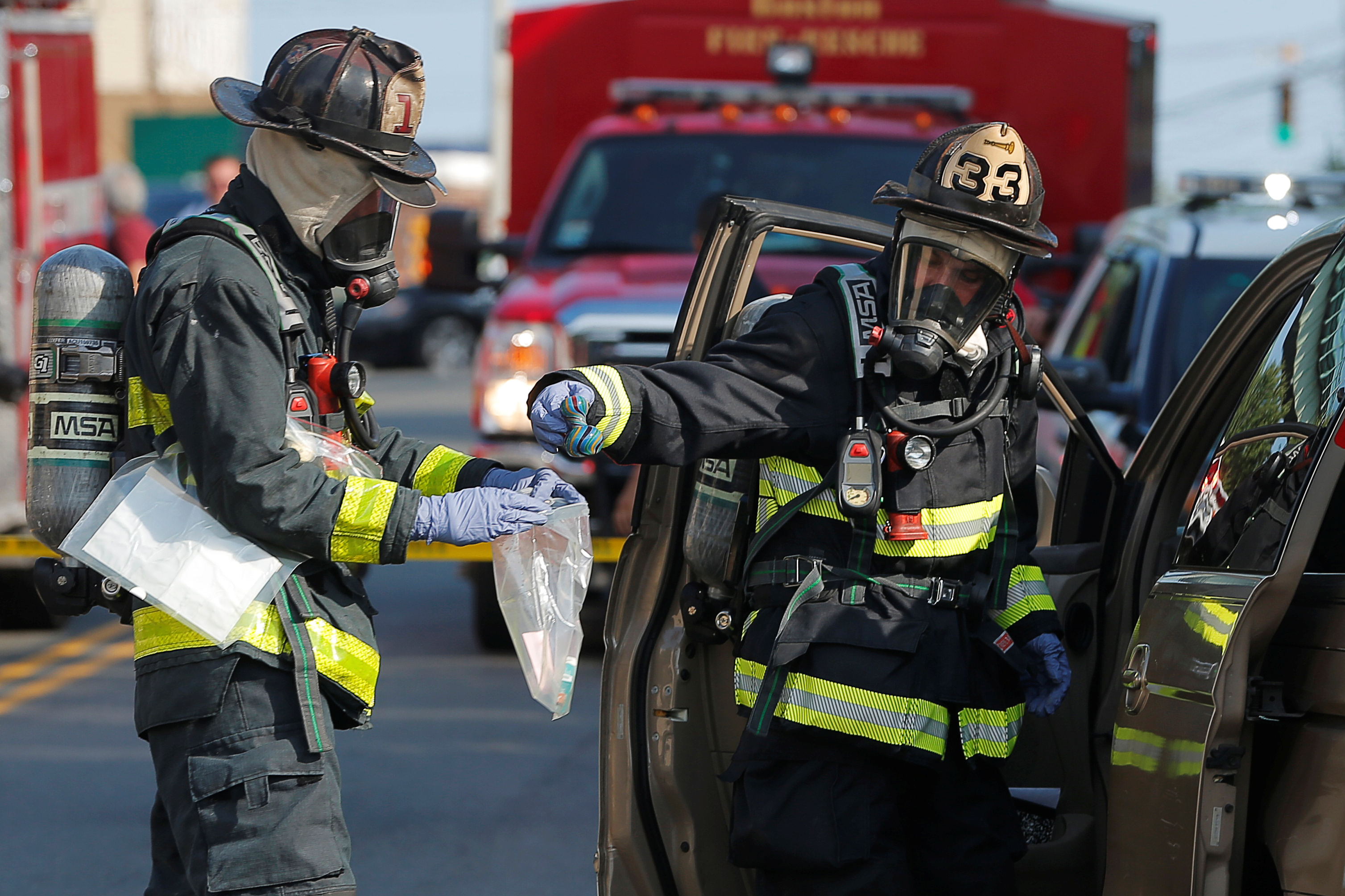 Firefighters in hazmat protection remove items from a vehicle in which several drug overdose victims were found, in addition to a powder believed to be fentanyl, in Chelsea, Massachusetts, U.S., August 4, 2017. REUTERS/Brian Snyder - RC1C0CD8F0B0