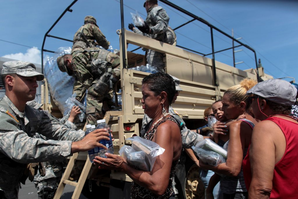 Soldiers of Puerto Rico's national guard distribute relief items to people, after the area was hit by Hurricane Maria in San Juan, Puerto Rico September 24, 2017. REUTERS/Alvin Baez TPX IMAGES OF THE DAY - RC1F1B442920