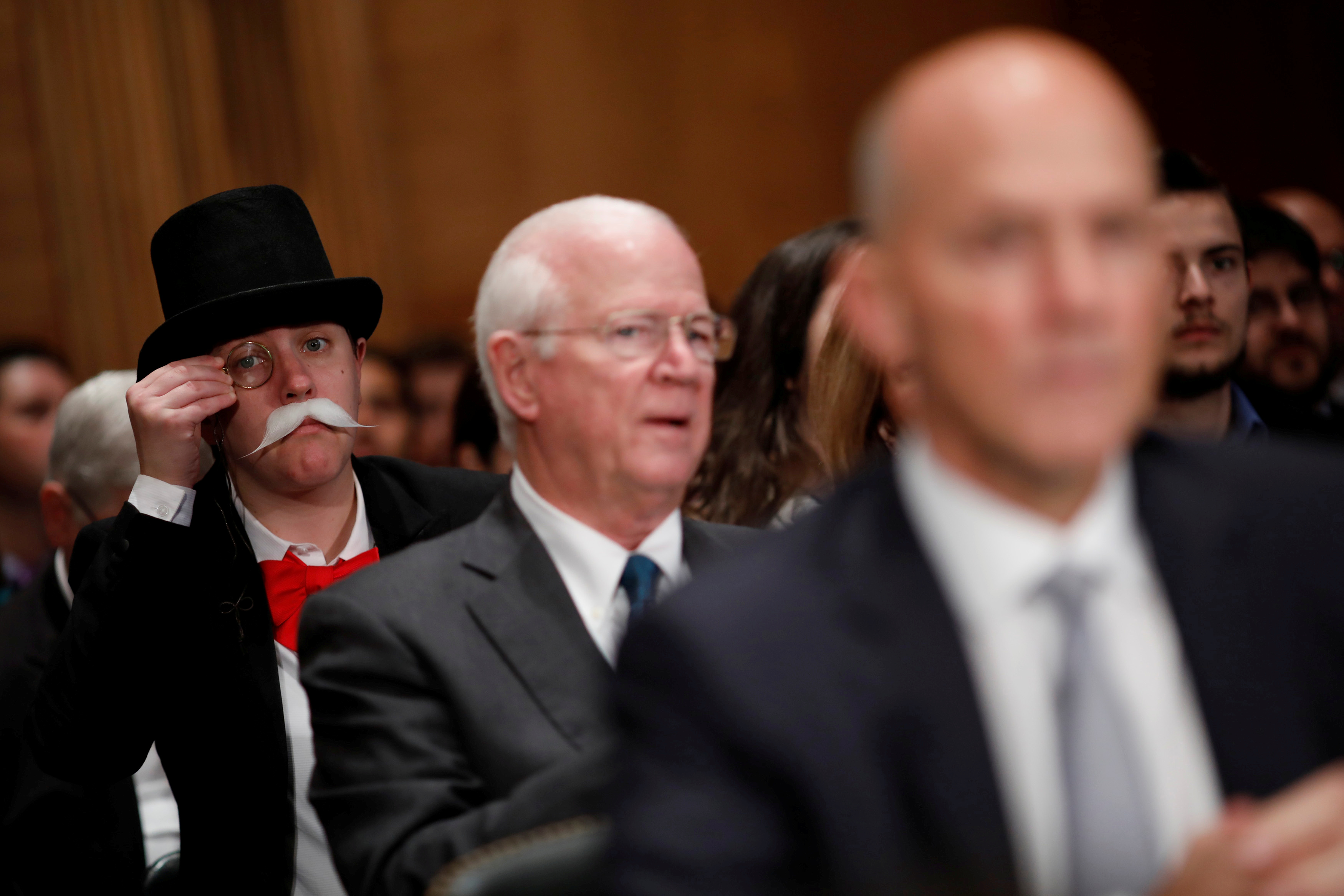 A hearing attendee dressed as the Monopoly Man looks on as Richard Smith, former chairman and CEO of Equifax, testifies before the U.S. Senate Banking Committee in Washington, D.C. Photo by Aaron P. Bernstein/Reuters