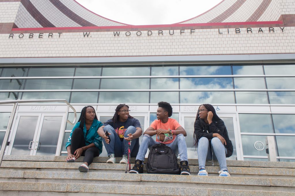 Clark Atlanta University students Destiny Rudolph, Delaina Mims, Charles Finch and Jewel Cannon meet on the steps of the Joseph W. Woodruff Library, which is shared among four Atlanta colleges and universities. Higher-education institutions increasingly are pooling their resources to cut costs. Photo: Jesse Pratt Lopez for The Hechinger Report