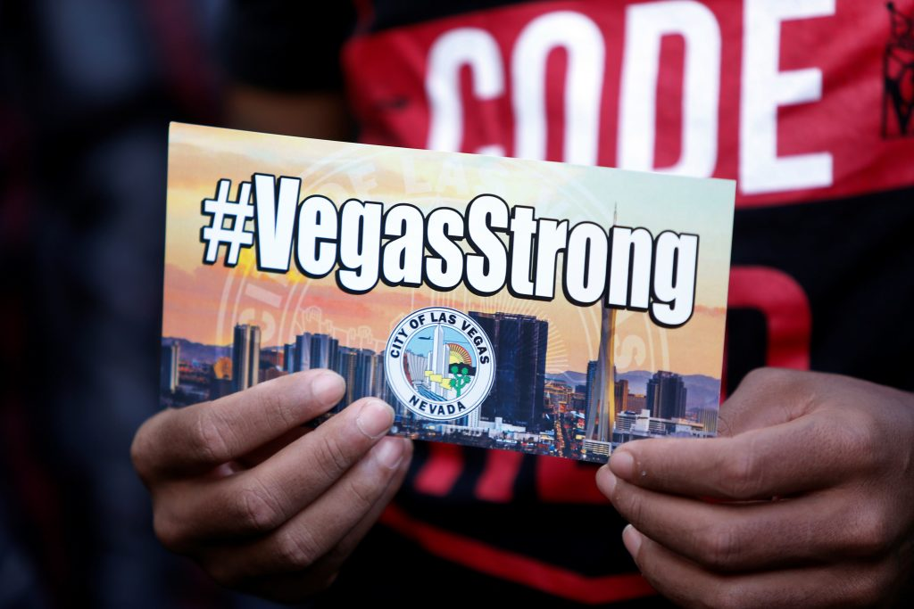 A man holds a sign with a VegasStrong hashtag during a prayer vigil, in honor of those affected by the shooting on the Las Vegas Strip, in front of Las Vegas City Hall in Las Vegas, Nevada, U.S. October 2, 2017. REUTERS/Las Vegas Sun/Steve Marcus - RC1378C157B0