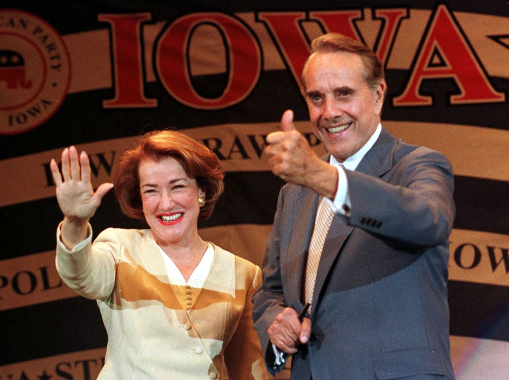 Republican presidential hopeful Elizabeth Dole and her husband former Sen. Bob Dole wave to the crowd inside the Hilton Coliseum where the Iowa Republicans held their annual straw poll August 14. [Elizabeth Dole is seeking a run at the White House, following her husband's failed attempt against President Clinton in 1996. Photo by Reuters