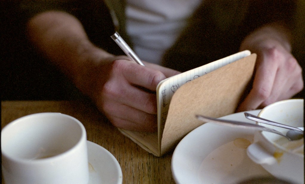 A writer sits in a cafe surrounded by teacups. He is writing in a notebook. The shot is a close up of his hands.. Photo by Getty creative