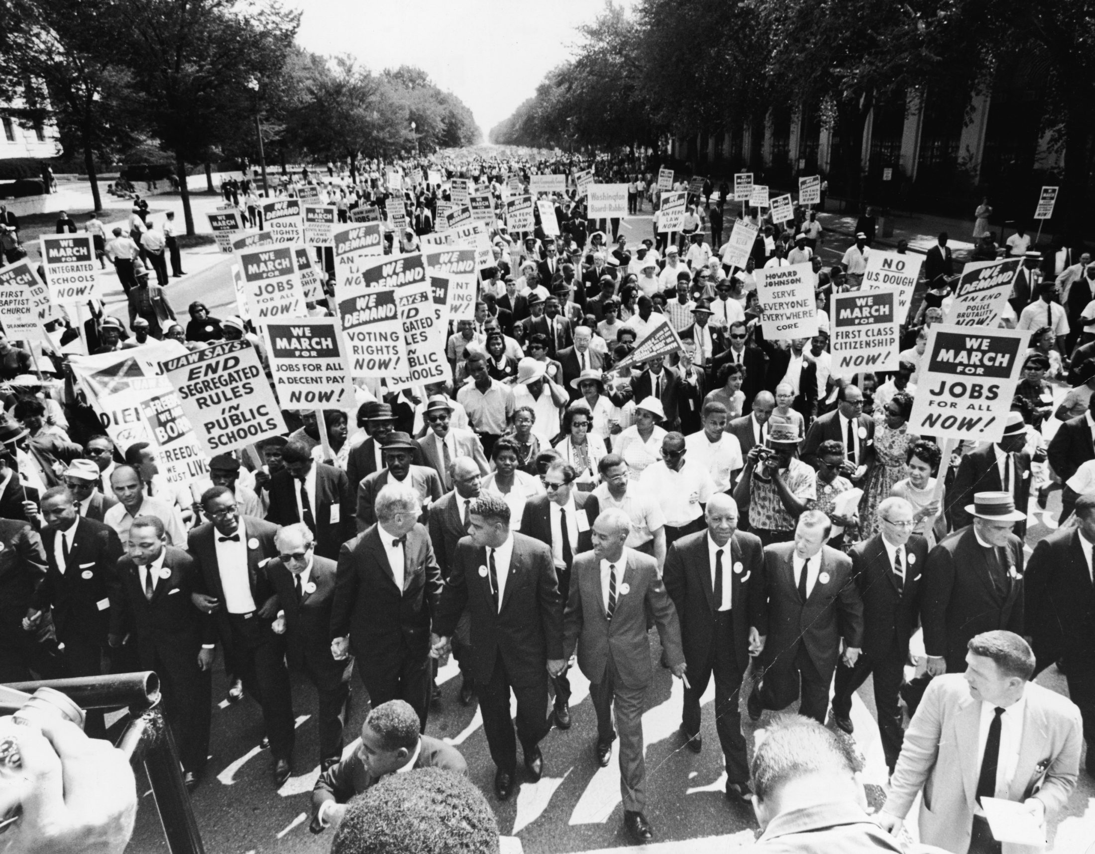Civil rights Leaders hold hands as they lead a crowd of hundreds of thousands at the March on Washington in 1963. Those in attendance include (front row): James Meredith and Martin Luther King, Jr., left; (L-R) Roy Wilkins, A. Phillip Randolph and Walther Reuther. Photo by Hulton Archive/Getty Images