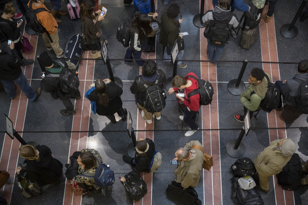 Passengers wait in the Transportation Security Administration (TSA) line at Ronald Reagan National Airport in Washington, ...