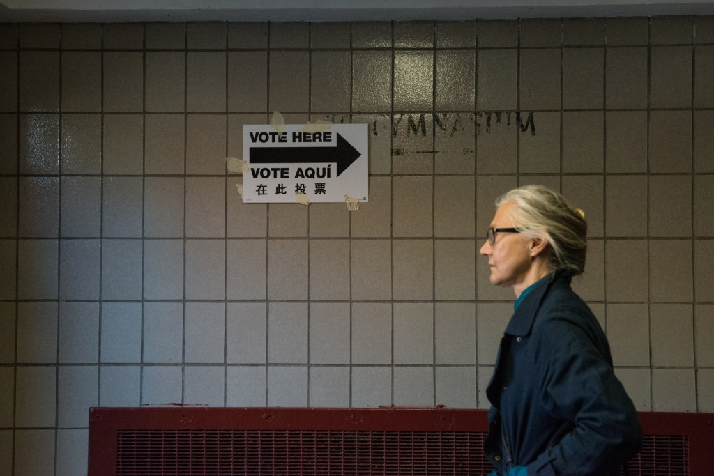 A woman walks past a voting sign at Public School 22 on April 19, 2016 in the Brooklyn borough of New York City. Photo by ...