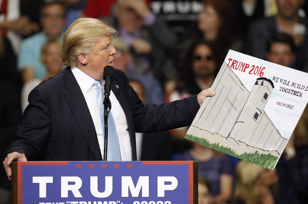 Then-Republican presidential candidate Donald Trump holds a sign supporting his plan to build a wall between the United States and Mexico that he borrowed from a member of the audience at his campaign rally in Fayetteville, North Carolina. Photo by Jonathan Drake/Reuters