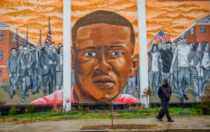A man walks past a mural of Freddie Gray in the Sandtown-Winchester neighborhood of Baltimore, Maryland. Photo taken December 2015. Photo by Bryan Woolston/Reuters