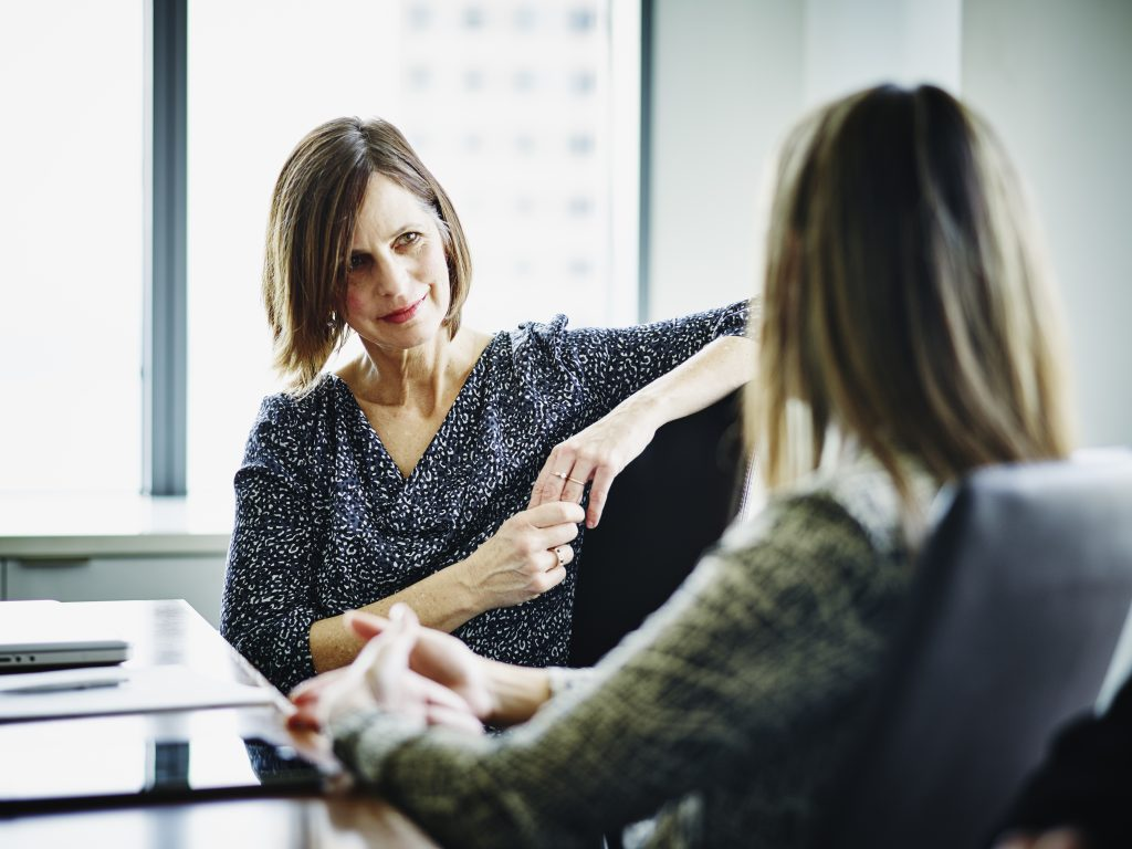 Businesswoman in discussion with female colleague at conference table in office.