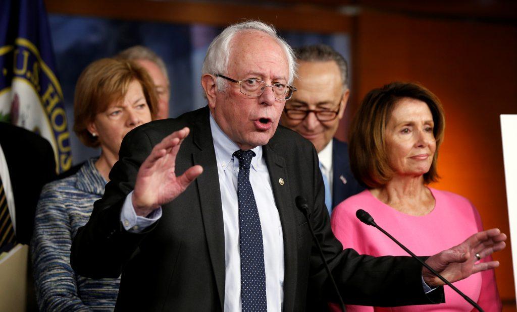 Former Democratic presidential candidate Bernie Sanders speaks to reporters as Senate Democratic Leader Chuck Schumer (2nd...