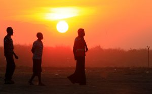 People who fled fighting in South Sudan are seen walking at sunset on arrival at Bidi Bidi refugee's resettlement camp near the border with South Sudan, in Yumbe district, northern Uganda December 7, 2016. REUTERS/James Akena - RTX2V727