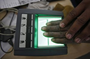 A villager goes through the process of a fingerprint scanner for UID database system at an enrolment centre at Merta district in Rajasthan