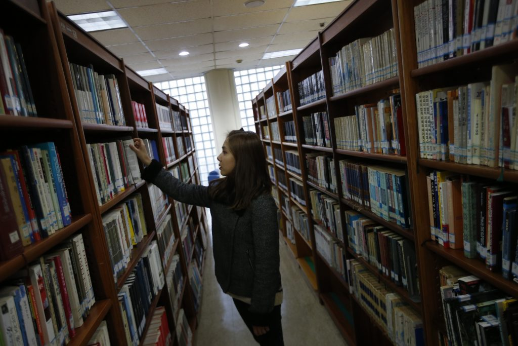 "Jang Ha-jin who was a trainee at S.M, Entertainment, picks out a book at a university library in Daejeon December 18, 2014. Jang made it to S.M. Entertainment's coveted training programme a decade ago after winning a talent contest. She stuck to a seven-day regimen for nearly three years, before giving it all up to return to a more sedate life. Thousands of Korean children dream of becoming household names like rapper Psy, whose 2012 ""Gangnam Style"" video was a global YouTube hit, often putting up with punishing schedules in the hope of one day making it big in the music industry. A recent survey of pre-teens shows that 21 percent of respondents wanted to be K-pop (Korean pop) stars when they grow up, the most popular career choice. REUTERS/Kim Hong-Ji (SOUTH KOREA - Tags: SOCIETY ENTERTAINMENT) ATTENTION EDITORS: PICTURE 13 OF 27 FOR WIDER IMAGE PACKAGE 'THE ROAD TO K-POP STARDOM' TO FIND ALL IMAGES SEARCH 'KIM K-POP' - RTR4MEYH"