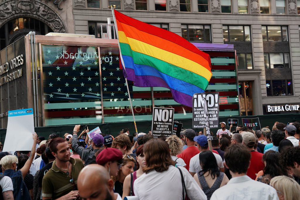 A rainbow flag flies as people protest U.S. President Donald Trump's announcement that he plans to reinstate a ban on transgender individuals from serving in any capacity in the U.S. military, in Times Square, in New York City, New York, U.S., July 26, 2017. REUTERS/Carlo Allegri - RTX3D279