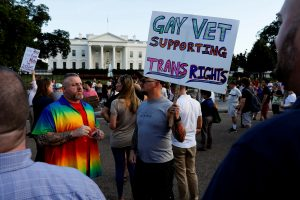 Demonstrators gather to protest U.S. President Donald Trump's announcement that he plans to reinstate a ban on transgender individuals from serving in any capacity in the U.S. military, at the White House in Washington, U.S. July 26, 2017. REUTERS/Jonathan Ernst - RTX3D29Q