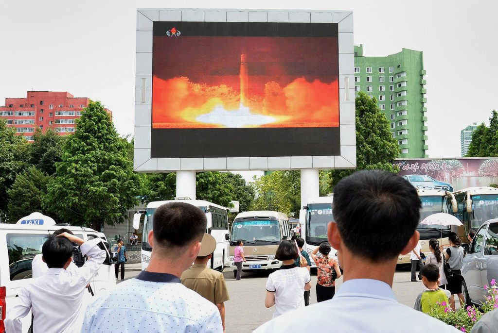 People watch news report showing North Korea's Hwasong-14 missile launch on electronic screen at Pyongyang station