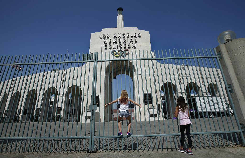 LOS ANGELES, CA - JULY 31: Gracey Peatrowsky, 11, left, and her friend Shannon Nash, 10, both of Orange, get a closer view of the peristyle end of the Los Angeles Memorial Coliseum in Los Angeles on July 31, 2017. Los Angeles has reached an agreement with Olympic leaders on terms that will pave the way for hosting the Summer Games of 2028 instead of 2024, according to a source close to the negotiation. The deal will bring the Olympics back to Southern California for a third time, after Los Angeles hosted the games in 1932 and 1984. (Mel Melcon/Los Angeles Times via Getty Images)