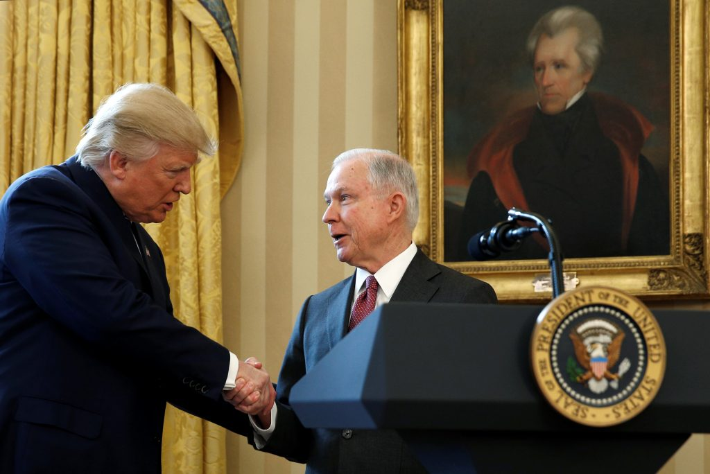 FILE PHOTO - Under a portrait of former President Andrew Jackson, U.S. President Donald Trump (L) congratulates Jeff Sessions after he was sworn in as U.S. Attorney General during a ceremony in the Oval Office of the White House in Washington, U.S. on February 9, 2017. REUTERS/Kevin Lamarque/File Photo - RTX3CVJF